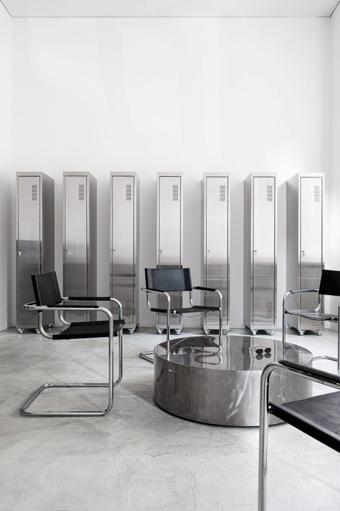 S34 chairs by Mart Stam with cylindrical chrome coffee table and lockers in tattoo parlour by Balbek Bureau
