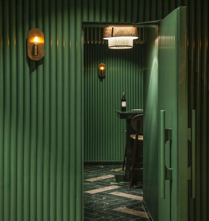 A green door opens into a bar