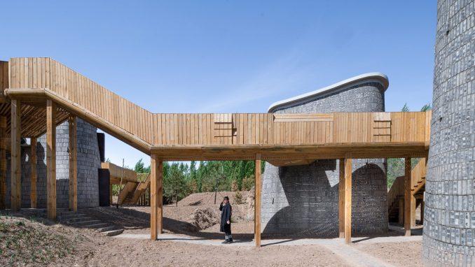 Person standing below wooden walkway connecting brick pods by Studio AVOID