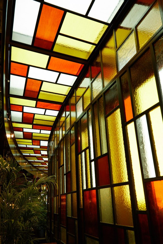 Wall of stained glass windows in restaurant interior by Pirajean Lees