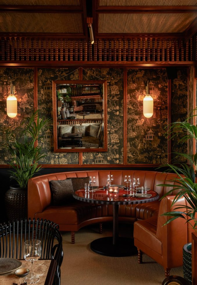 Restaurant seating area with curved leather booth, printed wallpaper and wooden joinery by Pirajean Lees