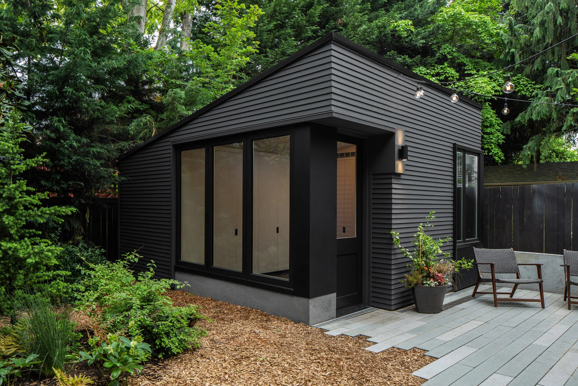 A black wooden shed in a garden in Seattle