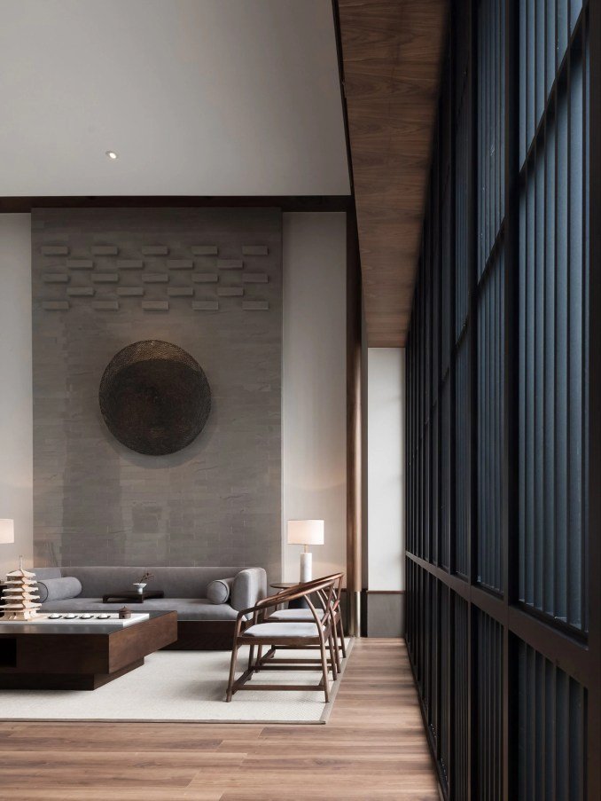 Lounge with wooden chairs and grey couch by JG Phoenix