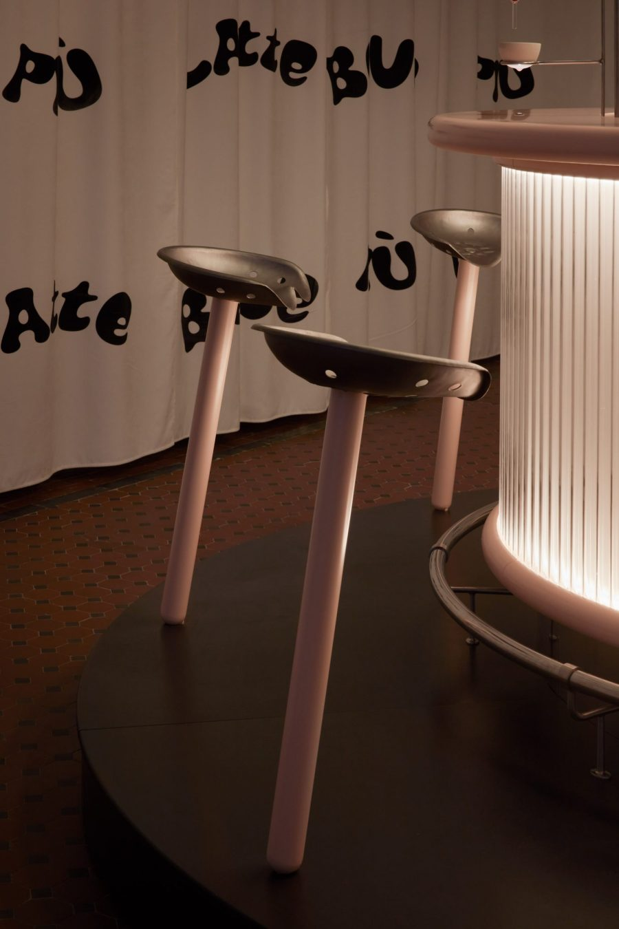 Stools with pink stems and metal tractor seats in installation by Lolita Gomez and Blanca Algarra Sanchez