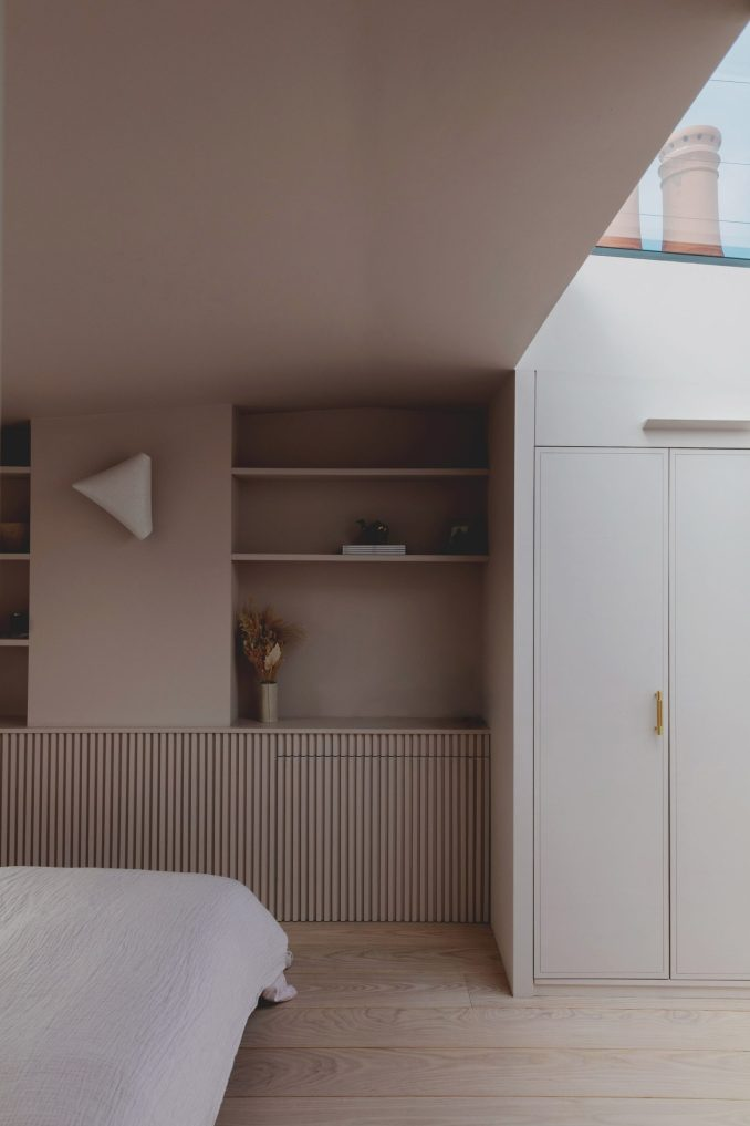 Shelves and closets in Bed and window in Narford Road loft extension by Emil Eve Architects