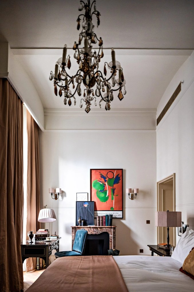 Hotel room by Roman and Williams with fireplace and art on the wall