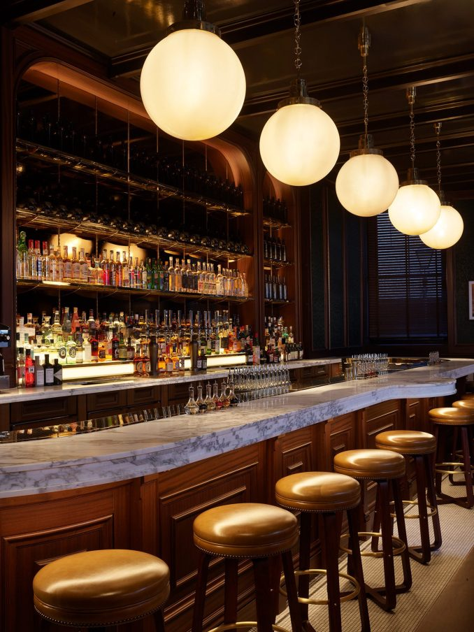Wood-fronted bar with marble top in NoMad London hotel