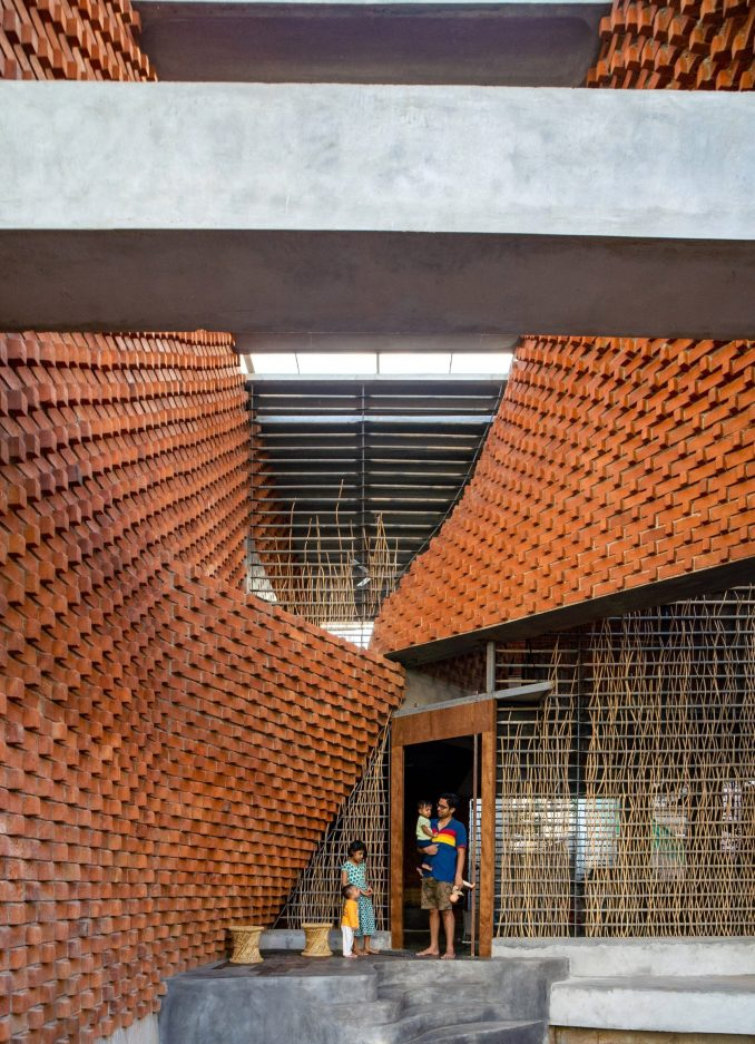 Brick walls twist between concrete surfaces at Pirouette House