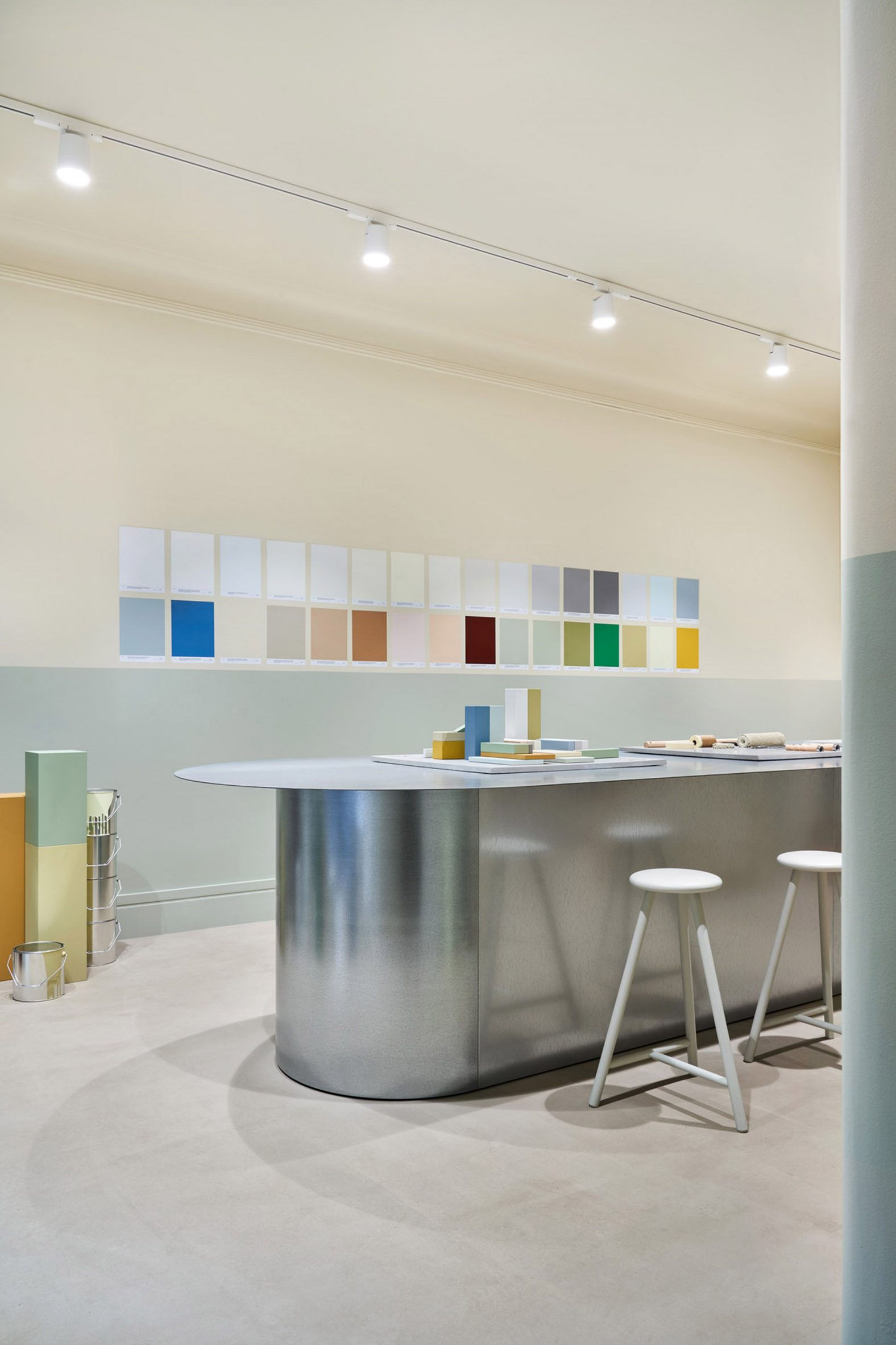 Galvanised steel table in front of a wall of paint swatches in the Cover Story Helsinki store