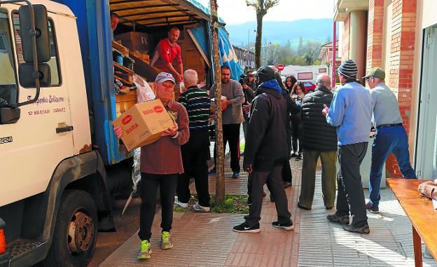 Descarga. Los voluntarios de Nagusilan proceden a llevar los alimentos al nuevo local donde se repartirán entre hoy y mañana. / AMAXKAR