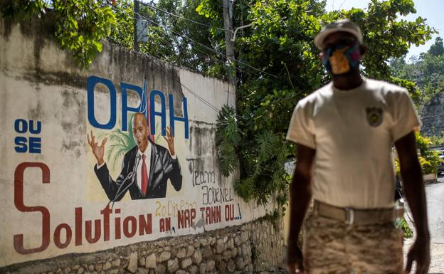 A policeman patrols a street in Port-au-Prince in front of a graffiti alluding to President Jovenel Moise.