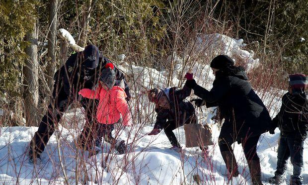 Kanadische Polizisten greifen Flüchtlinge auf. – REUTERS
