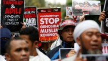 Protesters hold signs during a demonstration against what organisers say is the crackdown on ethnic Rohingya Muslims in Myanmar,