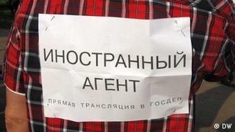Фото на тему СМИ-инстранных агентов: табличка Иностранный агент. Прямая трансляция в Госдеп, приколотая к рубашке на спине