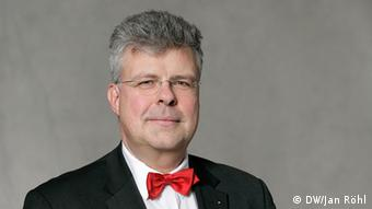 Christian Höppner wearing a red bow-tie and smiling at the camera.