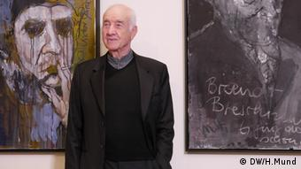 Mueller-Stahl standing in front of some of his paintings