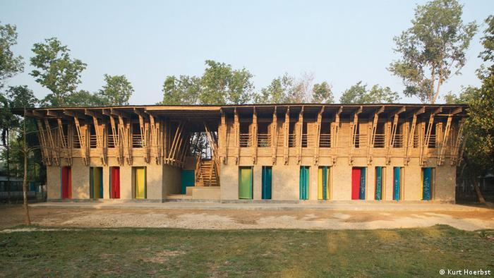 School in Bangledesh made of clay and wood with colorful curtains hanging from doorways.