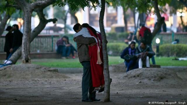 Homem em parque levantando uma mulher num abraço