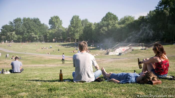 Germany, people sitting in the Görlitzer Park in Berlin drinking beer