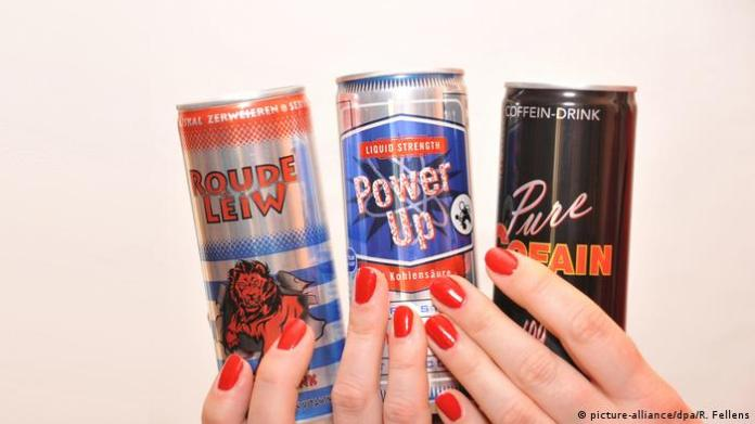 Two hands with painted fingernails hold several energy drinks (picture-alliance / dpa / R. Fellens)