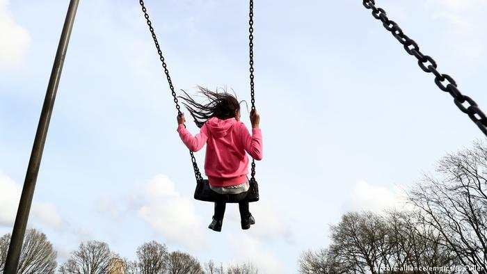 A girl playing on a swing