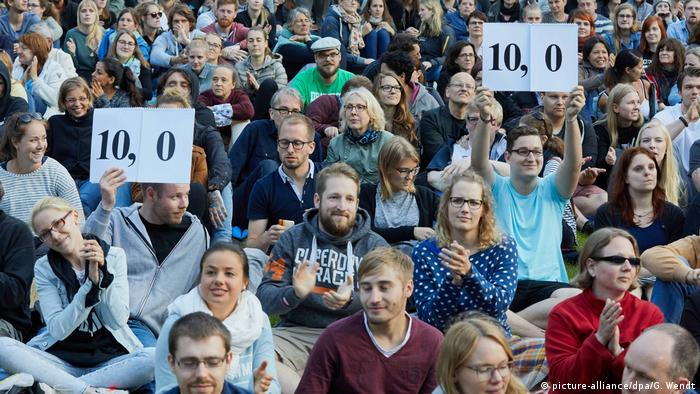 A crowd of people sitting outside on the grass at a poetry slam event in Germany in 2017.