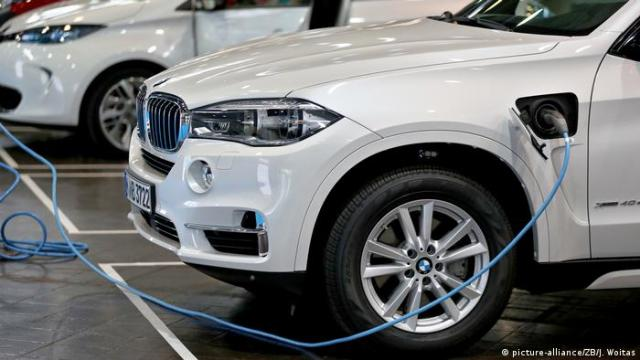 A BMW X5 in a showroom with a charging cable attached
