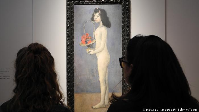 Two women looking at a painting of a woman holding a basket of flowers (picture-alliance/dpa/J. Schmitt-Tegge)