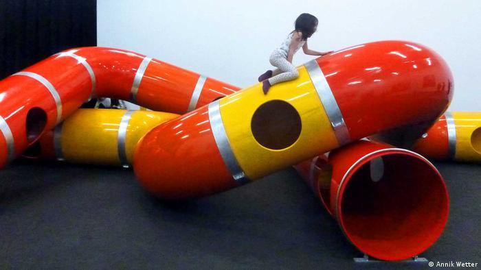 Mädchen klettert auf der Playground Project Ausstellung (Annik Wetter) auf Röhren