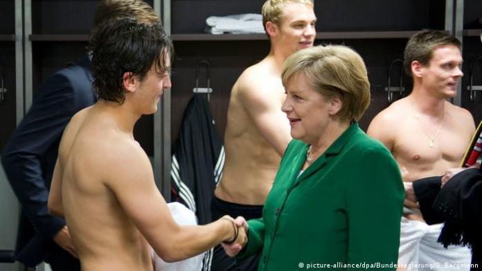 Mesut Özil meets Angela Merkel in a football changing room in 2010 (picture-alliance / dpa / Bundesregierung / G. Bergmann)