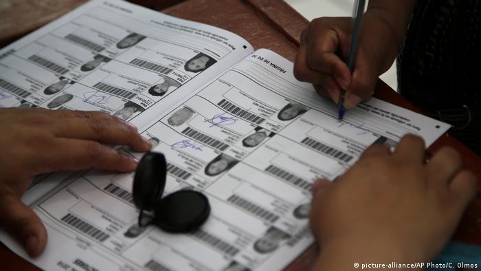 Foto simbólica de una persona que firma un padrón electoral en Perú