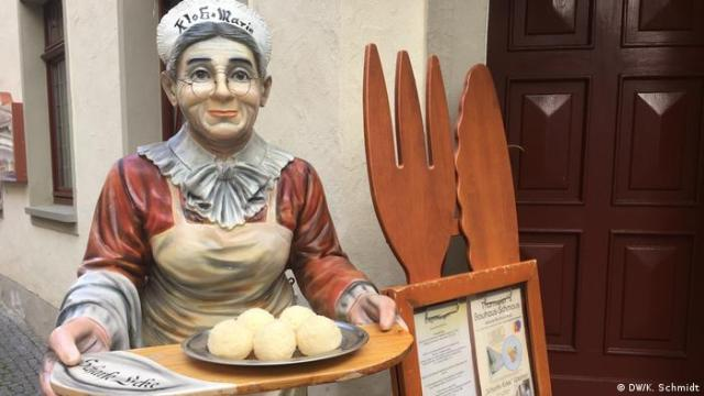 Statue of an old woman in an apron holding a tray with dumplings in front of the Scharfe Ecke restaurant in Weimar (DW/K. Schmidt)