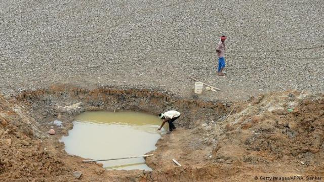 People collecting water a dried-out reservoir in Chennai, India