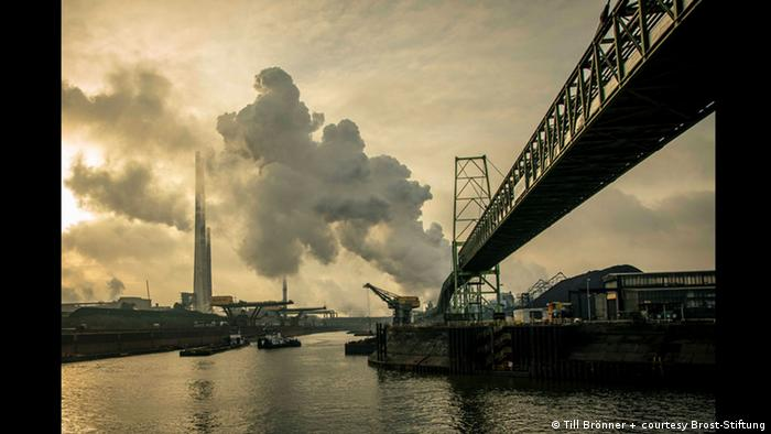 a photo of a bridge and smoke coming out of a factory chimney