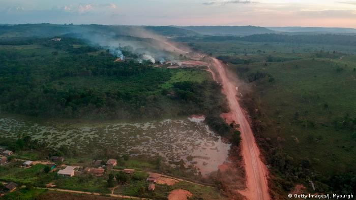 In this aerial view the red dust of the BR230 highway, known as Transamazonica, mixes with fires at sunset in the agriculture town of Ruropolis, Para state, northen Brazil