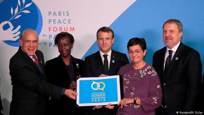 French President Emmanuel Macron, OECD Secretary General Angel Gurria and other UN officials hold a banner promoting gender equality at the Paris Peace Forum