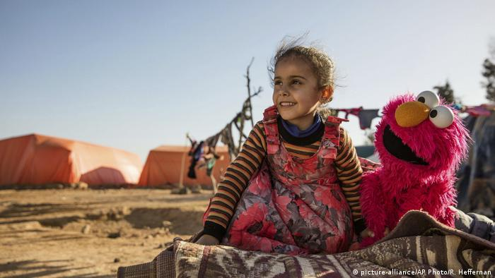 A girl plays with the Sesame Street character Elmo in an informal settlement in Jordan