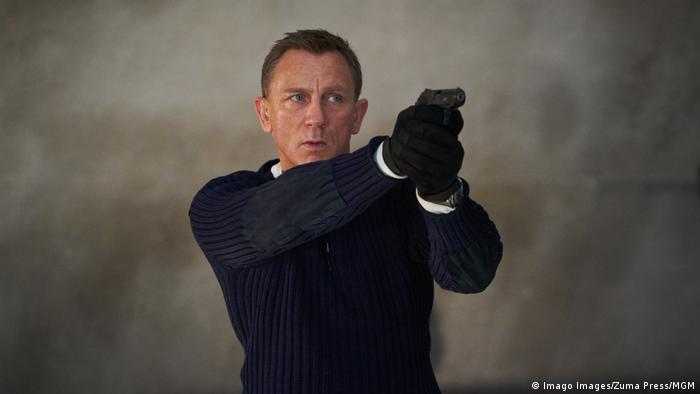 Daniel Craig in the role of James Bond, with a navy sweater, aiming a pistol.