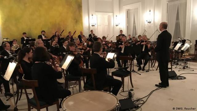Järvi leading the orchestra in the opulent Bellevue castle.