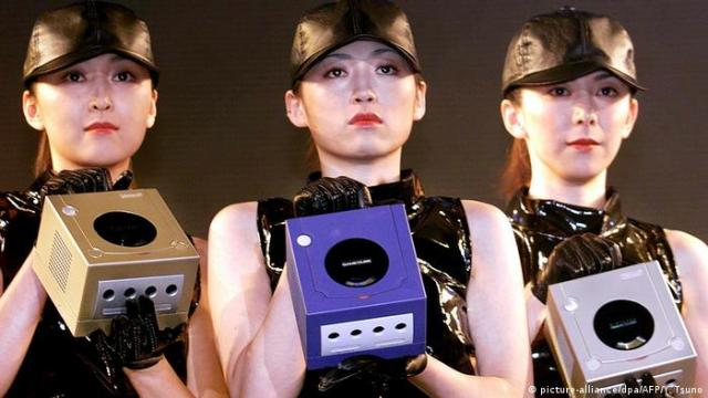 Three women hold game cubes Nintendo Gamecube (picture-alliance/dpa/AFP/Y. Tsuno)