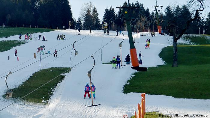 People skiing on slopes that do not have enough snow in Fischen im Allgäu, Germany