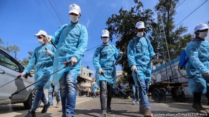 Palestinian workers spray disinfectant as a preventive measure amid fears of the spread of the coronavirus disease