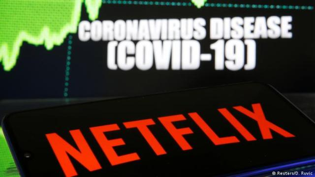 The Netflix logo is seen against a backdrop of a caption saying coronavirus disease [COVID-19]