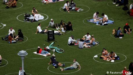 Personas sentadas sobre el césped, en círculos pintados para mantener la distancia social.