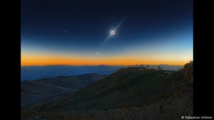 The sun is covered by the moon and shines beyond.  The sky is dark, a reddish stripe can be seen on the horizon, a star shines brightly next to the sun (Photo: Sebastian Voltmer).