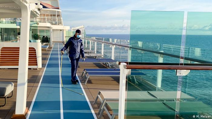 A person measures the distance between chair and chair on the deck of a ship