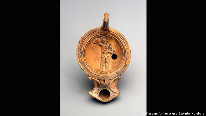 An orange clay lamp features a carving of a gladiator holding a sword and shield (Museum für Kunst und Gewerbe Hamburg)