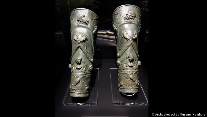 Two metal leg shields are ornately decorated with figures of people and animals. (Archäologisches Museum Hamburg)