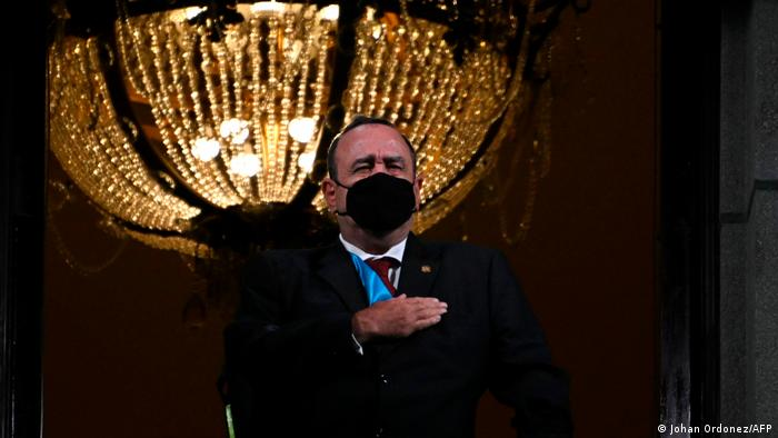 Alejandro Giammattei wears a black face mask and stands in front of a large chandelier