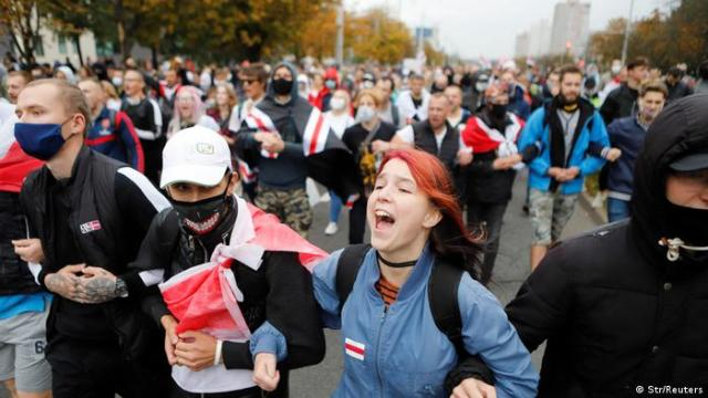 Column of protesters with white-red-white flags